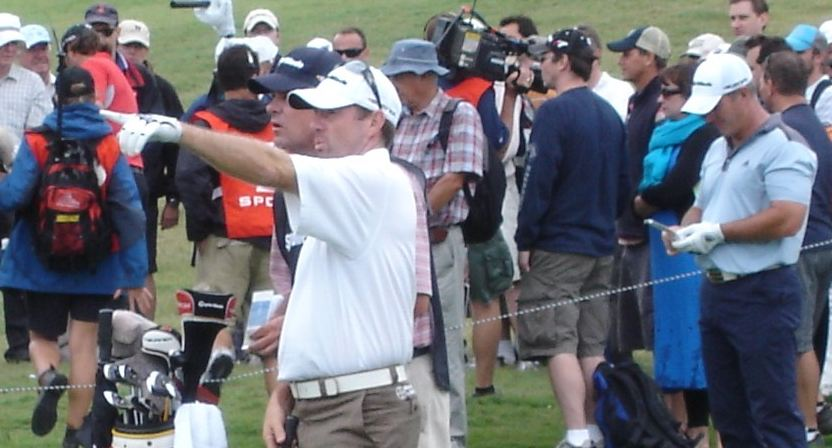 Rod Pampling points the way from the middle of a Royal Sydney fairway at the Australian Open. Mathew Goggin and his ball are embedded in the crowd at back and Peter Lonard knows the direction but not the distance.