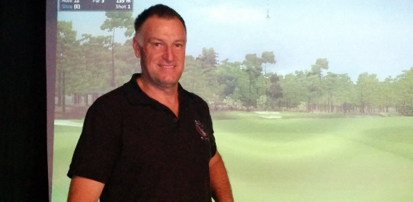 "Ex-caddie Stuart Dryden in front of the ""12th hole at Augusta National"""
