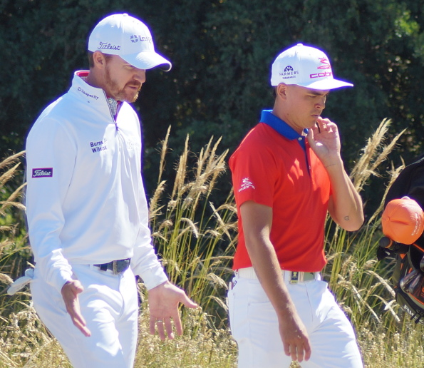 Americans Jimmy Walker and Rickie Fowler seemingly deep in tactical discussion on their way to a 2-under finish, just one behind the leaders